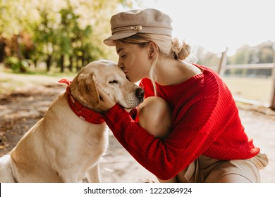 Beautiful blonde girl kissing her adorable dog in the autumn sunny park. Stylish young woman in red sweater and trendy hat holding tenderly the pet.