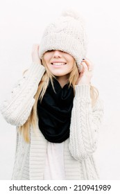 Beautiful blonde girl with knitted beanie on her face. Smiling