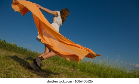 BEAUTIFUL BLONDE GIRL LAUGHS AND DANCES OUTDOORS WITH AN ORANGE SCARF IN HER HANDS ON A MEADOW DURING SUNSET
