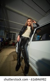 beautiful blonde girl in leather clothes in the garage