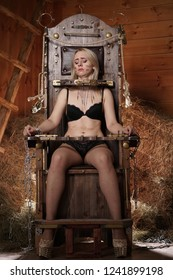 beautiful blonde girl in lingerie on chair for torture suffering in barn with hay