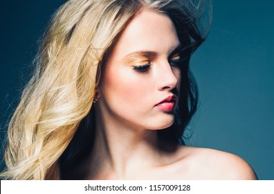 Beautiful blonde girl with long fly hair and pink lips studio female portrait