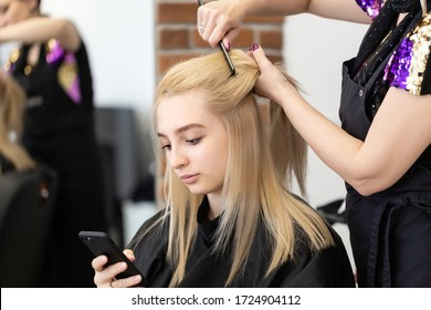 Beautiful blonde girl with long straight hair sits in a chair in a beauty salon. A professional hairdresser makes a girl curling after dyeing hair. The girl uses the phone during the procedure.