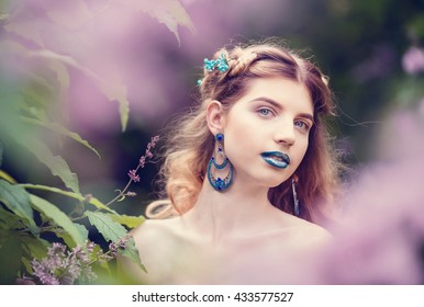 Beautiful blonde girl with long wavy curls in the park among the lilacs, stunning makeup, closeup, portraits, headshot