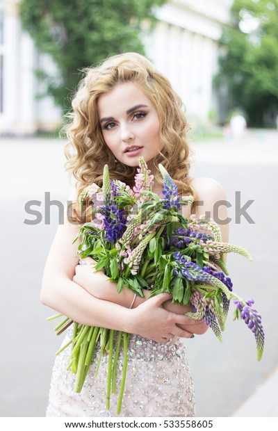 Beautiful blonde girl in a luxurious shiny evening dress with a bouquet of flowers in her hand is on the background of a country residence