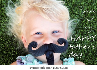 beautiful blonde girl  lying  on the grass  with mustache. Happy father`s day