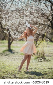 Beautiful blonde girl in mini pink dress wearing bunny ears posing in the spring garden. Vogue fashion concept.