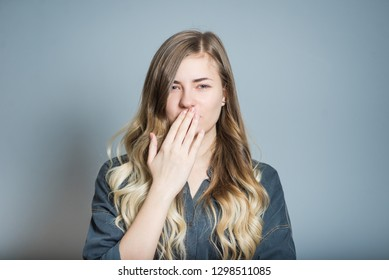 Beautiful blonde girl nauseous and puts hand over mouth, isolated on gray background