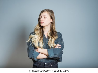 Beautiful blonde girl offended crossed arms, isolated on gray background