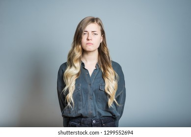 Beautiful blonde girl offended isolated on gray background