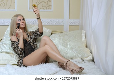 The beautiful blonde girl on a bed does makeup