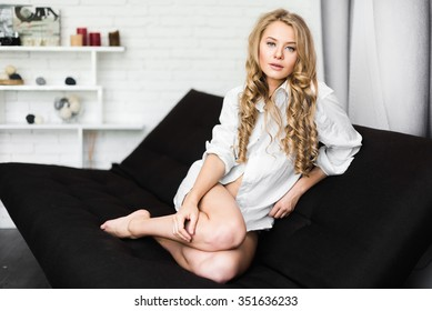 Beautiful blonde girl on a chair in a white shirt