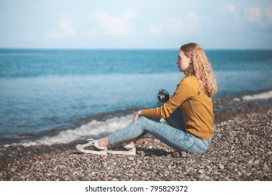 beautiful blonde girl on a sea beach with a old camera in hand.