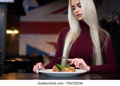 So beautiful blonde girl in perfect place with english interior looks great in red warm dress she eats delicious food and relaxing