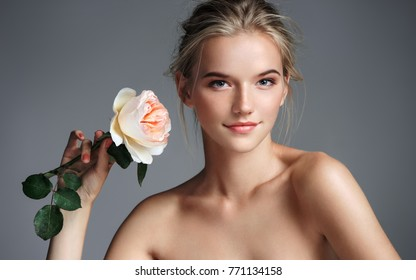 Beautiful blonde girl. Photo of young girl with rose on grey background. Beauty & Skin care concept