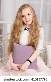 Beautiful blonde girl with pillow in hands. Female portrait in studio.