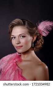 The beautiful blonde girl in a beautiful pinkostrich feather dress on black background. pleasant-looking Caucasian female looking happily in camera, emotional portrait