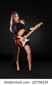 Beautiful blonde girl playing guitar in rock style on a black background