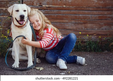 Beautiful blonde girl playing with her dog. Outdoor portrait. series