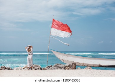 beautiful blonde girl posing on the beach next to boat and flag of indonesia