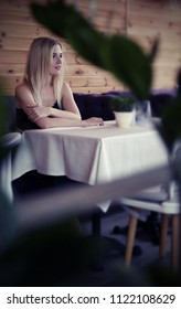 Beautiful blonde girl posing while sitting in a cozy cafe. She wears a black lace tops and blue jeans. on purple sofa, game peeping, the global march, active woman series