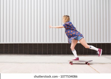 Beautiful and blonde girl practicing long board on the bridge
