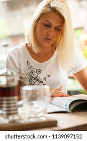 Beautiful blonde girl reading magazine in cafe, outdoor, with coffee on the table, some film grain