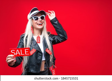 Beautiful blonde girl with red price tags hang on stylish leather clothes. Young bright woman in sunglasses is ready to big sale. Black friday concept. Special best offer deal to buy cheap goods.