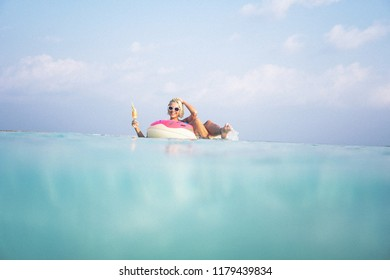 Beautiful blonde girl relaxing in her doughnut floaty