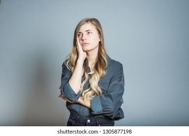 Beautiful blonde girl is sad and tired, isolated on gray background