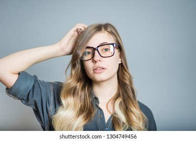 Beautiful blonde girl scratches head, confused, wears glasses, isolated on gray background