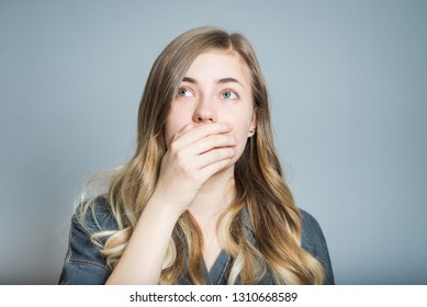 Beautiful blonde girl is shocked and covers her mouth with her hands, isolated on gray background