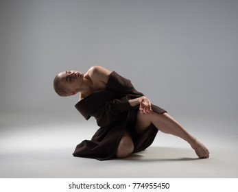 Beautiful blonde girl. With a short hairstyle. Bald head. In plastic dance.