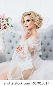 Beautiful blonde girl sitting on a sofa dressed in a white negligee holding a wedding bouquet, sending an air kiss in the background many colors