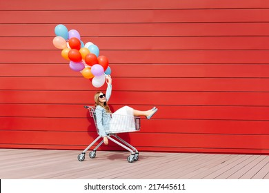 beautiful blonde girl sitting in shopping cart, holding color balloons in her hand. Sunny day, outside