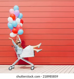 Beautiful blonde girl sitting in shopping cart, color balloons in her one hand. Smiling, laughing. Sunny day, outside