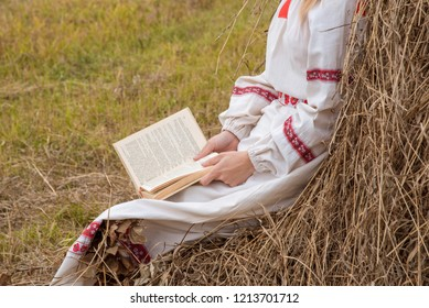 Beautiful blonde girl in a Slavic dress reads a book at a haystack in autumn