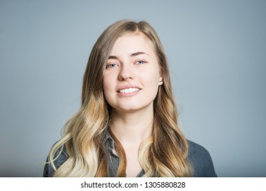 Beautiful blonde girl smiling happy isolated on gray background