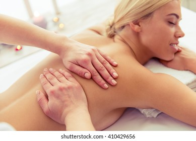 Beautiful blonde girl is smiling, lying with closed eyes on front of her body while a massage therapist is massaging her back