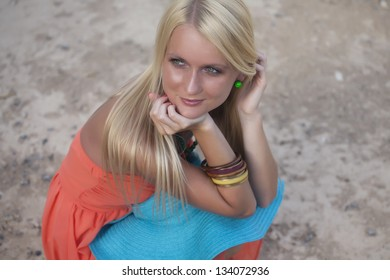 Beautiful blonde girl smiling and waiting for a boy on the beach
