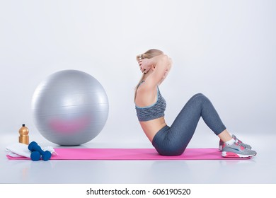 beautiful blonde girl in sportswear does exercises on a fitness Mat on a gray background