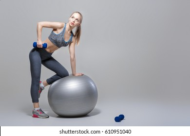 beautiful blonde girl in sportswear does exercises with dumbbells on fitness ball on grey background