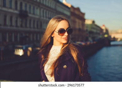 beautiful blonde girl in sunglasses posing on the street near the river in the violet cloak