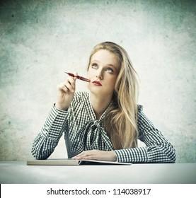 Beautiful blonde girl thinking while writing