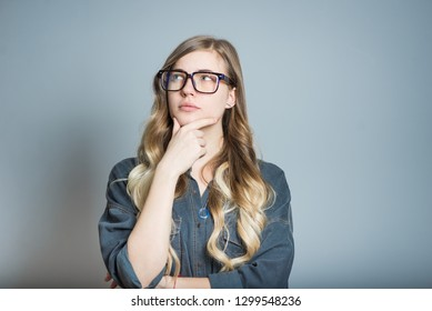 Beautiful blonde girl thought about the problem, wears glasses, isolated on gray background