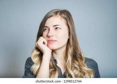 Beautiful blonde girl in thought isolated on gray background