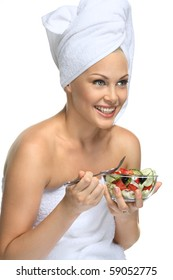 Beautiful blonde girl in towel eating fresh salad and smiling