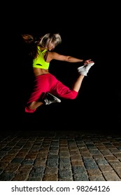 Beautiful blonde girl training at night on old pavement made of old stone tiles. Picture with black copy space.