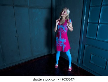Beautiful blonde girl with two pigtails, with creative make-up: pink glossy lips, wearing pink skeleton dress. for the Halloween party. Close up