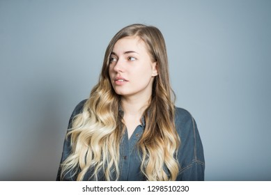 Beautiful blonde girl unpleasantly surprised, isolated on gray background